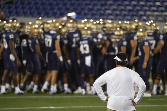 Navy head coach Ken Niumatalolo looks on as his team huddles before an NCAA college football game against BYU, Monday, Sept. 7, 2020, in Annapolis, Md. (AP Photo/Tommy Gilligan)