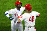 Philadelphia Phillies' Andrew McCutchen, left, and Bryce Harper celebrate after McCutchen's two-run home run off Atlanta Braves pitcher Robbie Erlin during the third inning of a baseball game, Friday, Aug. 28, 2020, in Philadelphia. (AP Photo/Matt Slocum)