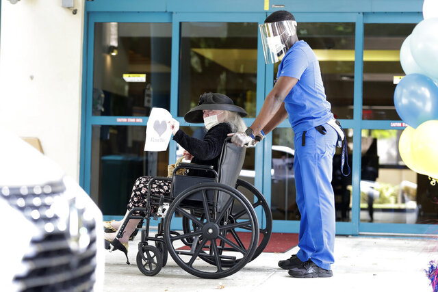 Margaret Choinacki, center, 87, who has no other family members left because her husband and daughter have died, waves goodbye after a drive-by visit by her friend Frances Reaves, as resident care coordinator Anggy Volmar, right, wheels her back inside, Friday, July 17, 2020, at Miami Jewish Health in Miami. Miami Jewish Health has connected more than 5,000 video calls and allowed drive-by visits where friends and family emerge through sunroofs to see their loved ones. (AP Photo/Wilfredo Lee)