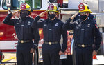 Anaheim firefighters salute as the procession carrying fallen firefighter Charles Morton, killed while battling a blaze in the mountains east of Los Angeles, along Hewes Street in Orange, Calif., Tuesday, Sept. 22, 2020, from San Bernardino to the Ferrara Colonial Mortuary in Orange. Morton, 39, a San Diego native, was a 14-year veteran of the U.S. Forest Service and a squad boss for the Big Bear Interagency Hotshots in San Bernardino National Forest, officials said.  (Mark Rightmire/The Orange County Register via AP)