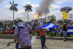 An anti-government protester fires a homemade mortar on the sidelines of a Stations of the Cross procession on Good Friday in Managua, Nicaragua, Friday, April 19, 2019. Good Friday religious processions in Nicaragua's capital have taken a decidedly political tone as people have seized on a rare opportunity to renew protests against the government of President Daniel Ortega. (AP Photo/Alfredo Zuniga)