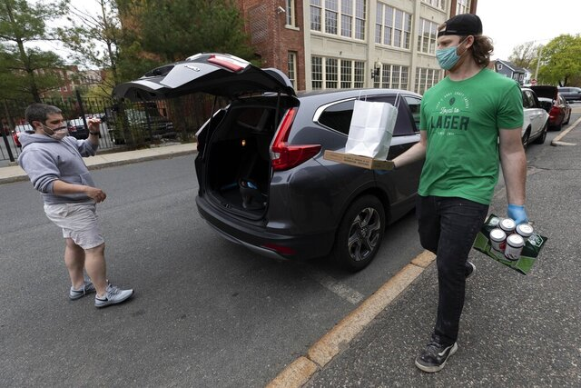 In this Friday, May 8, 2020, photo, Jack's Abby craft brewery employee Andrew Kelley carries an order to a customer in a line of cars waiting curbside in Framingham, Mass. Sales of wine, spirits and other alcoholic beverages have risen during the coronavirus pandemic. (AP Photo/Michael Dwyer)