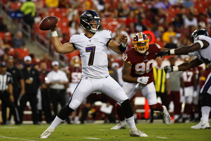 Baltimore Ravens quarterback Trace McSorley (7) throws the ball with Washington Redskins linebacker Montez Sweat (90) behind him during the first half of an NFL preseason football game Thursday, Aug. 29, 2019, in Landover, Md. (AP Photo/Alex Brandon)