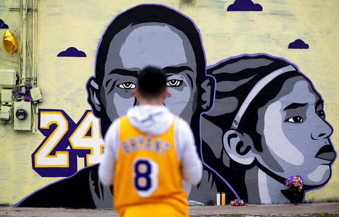 Omar Garcia, wearing Kobe Bryant's jersey, looks at a new tribute mural honoring Kobe Bryant and his daughter, Gianna, on Thursday, Jan. 30, 2020, in Austin, Texas. The mural, located behind the Sushi Hi restaurant along Guadalupe Street, was created by Texas-based artist Laced and Found with help from Snuk One and Riki Loring. (Nick Wagner/Austin American-Statesman via AP)