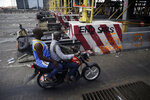 People drive past burnt toll gates with anti police slogans sprayed across, in Lagos Friday, Oct. 23, 2020. Resentment lingered with the smell of charred tires Friday as Nigeria's streets were relatively calm after days of protests over police abuses, while authorities gave little acknowledgement to reports of the military killing at least 12 peaceful demonstrators earlier this week. (AP Photo/Sunday Alamba)