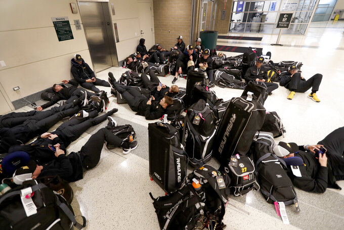 Players with the University of Missouri baseball team wait in the baggage claim area of Chicago's Midway Airport Thursday, March 12, 2020, only to arrive in Chicago and then get notified that the team's SEC Conference opener with Alabama Friday, had been canceled. (AP Photo/Charles Rex Arbogast)