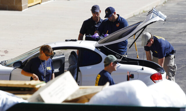 FILE—In this Friday, July 20, 2012, file photo, investigators examine a vehicle parked outside a back exit at the Century 16 movie theater east of the Aurora Mall in Aurora, Colo. A gunman in a gas mask barged into a crowded Denver-area theater during a midnight showing of the Batman movie, hurled a gas canister and then opened fire in one of the deadliest mass shootings in recent Colorado history. On Monday, June 29, 2020, the Colorado Supreme Court upheld the state's ban on large capacity gun magazines, the law put into effect a year after the mass shooting in Aurora. (AP Photo/David Zalubowski, File)