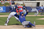 Texas Rangers' Nolan Fontana scores behind Milwaukee Brewers catcher Yasmani Grandal on a sacrifice fly by Willie Calhoun in the sixth inning of a spring training baseball game Tuesday, March 19, 2019, in Phoenix (AP Photo/Sue Ogrocki)