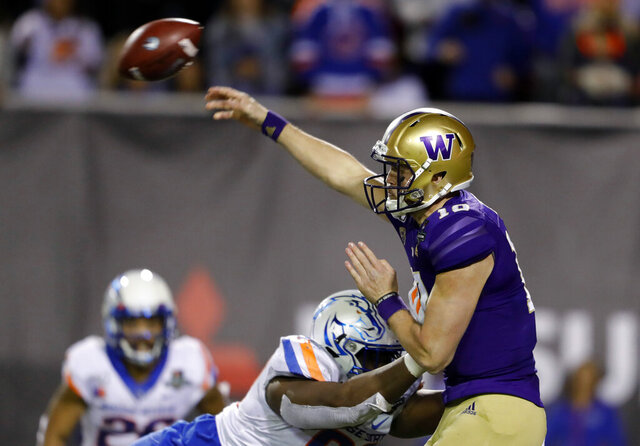 Washington quarterback Jacob Eason (10) passes under pressure from Boise State nose tackle Scale Igiehon (90) during the second half of the Las Vegas Bowl NCAA college football game at Sam Boyd Stadium, Saturday, Dec. 21, 2019, in Las Vegas. (AP Photo/Steve Marcus)