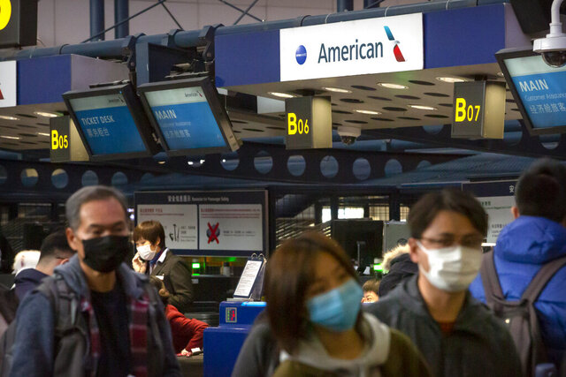 Travelers wearing face masks line up to check in for an American Airlines flight to Los Angeles at Beijing Capital International Airport in Beijing, Thursday, Jan. 30, 2020. China counted 170 deaths from a new virus Thursday and more countries reported infections, including some spread locally, as foreign evacuees from China's worst-hit region returned home to medical observation and even isolation. (AP Photo/Mark Schiefelbein)