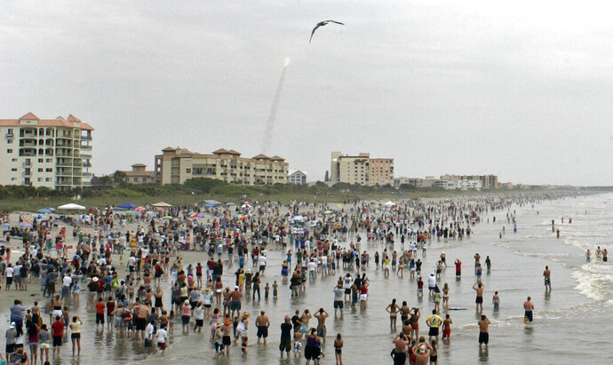 FILE - In this Friday, July 8, 2011 file photo, crowds gather in the surf and on the beach in Cocoa Beach, Fla., to watch the launch of the space shuttle Atlantis on STS-135. This is the final U.S. shuttle mission before the fleet is retired. In ordinary times, the beaches and roads along Florida's Space Coast would be packed with hundreds of thousands of spectators, eager to witness the first astronaut launch from Florida in nine years, scheduled for May 27, 2020. In the age of coronavirus, local officials and NASA are split on whether that's a good idea. (AP Photo/Dave Martin)