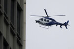 A New South Wales police helicopter patrols the sky over the central business district in Sydney, Australia, Saturday, Aug. 21, 2021. Police are enforcing a CBD exclusion zone in an effort to stop an anti-lockdown protest scheduled for Saturday. (AP Photo/Mark Baker)