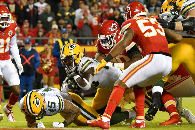 Green Bay Packers running back Jamaal Williams, center, scores a touchdown between Packers fullback Danny Vitale (45), Kansas City Chiefs linebacker Anthony Hitchens (53) and Chiefs defensive end Emmanuel Ogbah, second from right, during the first half of an NFL football game in Kansas City, Mo., Sunday, Oct. 27, 2019. (AP Photo/Ed Zurga)