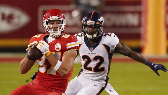 Kansas City Chiefs tight end Travis Kelce (87) catches a pass as Denver Broncos strong safety Kareem Jackson (22) defends in the first half of an NFL football game in Kansas City, Mo., Sunday, Dec. 6, 2020. (AP Photo/Charlie Riedel )