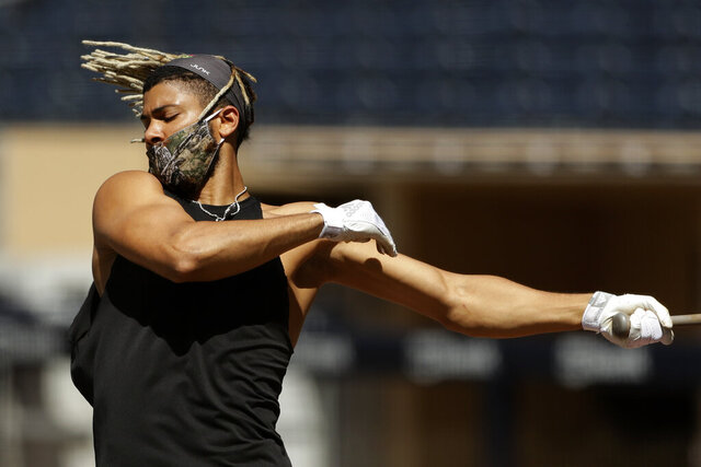 FILE - In this July 6, 2020, file photo, San Diego Padres shortstop Fernando Tatis Jr. bats during baseball training in San Diego. Tatis, has become one of the faces of the San Diego Padres, with or without a facemask. The exciting young shortstop has been taking coronavirus protocols seriously, including wearing a mask during summer camp workouts.  (AP Photo/Gregory Bull,File)