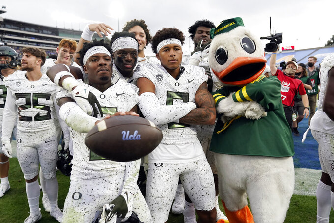 Oregon players and mascot celebrate a win over UCLA in an NCAA college football game Saturday, Oct. 23, 2021, in Pasadena, Calif. (AP Photo/Marcio Jose Sanchez)