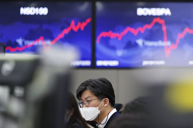 A currency trader watches computer monitors at the foreign exchange dealing room in Seoul, South Korea, Wednesday, Dec. 23, 2020. Asian stock markets rose Wednesday after President Donald Trump suggested he may veto a $900 billion economic aid package. (AP Photo/Lee Jin-man)