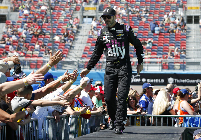 Jimmie Johnson is greeted by fans during driver introductions prior to the start of the NASCAR Cup Series auto race at ISM Raceway, Sunday, March 10, 2019, in Avondale, Ariz. (AP Photo/Ralph Freso)