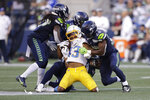 Los Angeles Chargers wide receiver Tyron Johnson, center, is brought down by Seattle Seahawks' Marquise Blair, Damarious Randall and Ugo Amadi, from left, during the first half of an NFL football preseason game Saturday, Aug. 28, 2021, in Seattle. (AP Photo/John Froschauer)