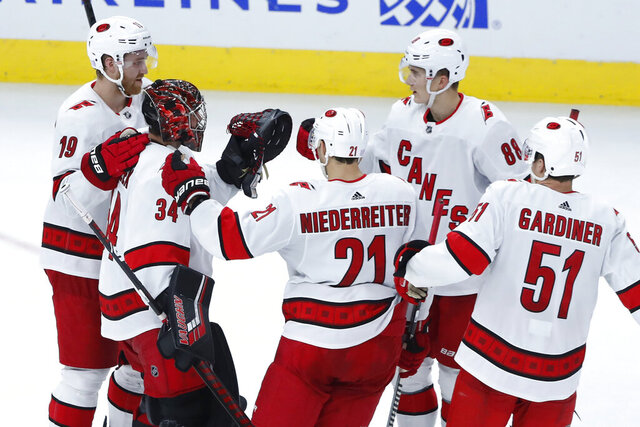 The Carolina Hurricanes gather around goaltender Petr Mrazek (34) to celebrate the team's 4-2 win over the Chicago Blackhawks in an NHL hockey game Tuesday, Nov. 19, 2019, in Chicago. (AP Photo/Charles Rex Arbogast)