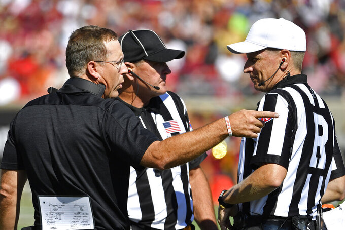 Louisville head coach Scott Satterfield, left, argues a call with a referee during the second half of an NCAA college football game in Louisville, Ky., Saturday, Oct. 5, 2019. Louisville won 41-39. (AP Photo/Timothy D. Easley)