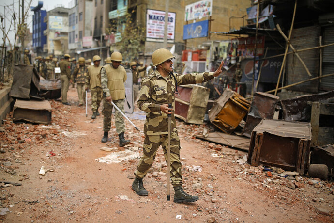 An Indian paramilitary soldier asks residents to stay indoors as they patrol a street vandalized in Tuesday's violence in New Delhi, India, Thursday, Feb. 27, 2020. India accused a U.S. government commission of politicizing communal violence in New Delhi that killed at least 30 people and injured more than 200 as President Donald Trump was visiting the country. The violent clashes between Hindu and Muslim mobs were the capital's worst communal riots in decades and saw shops, Muslim shrines and public vehicles go up in flames. (AP Photo/Altaf Qadri)
