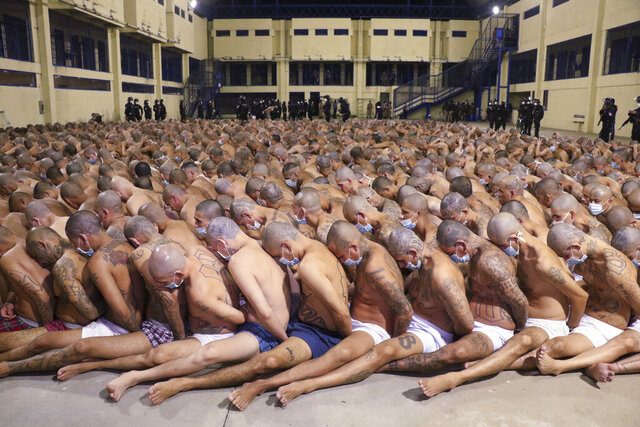In this photo released by the El Salvador Presidency Press Office, inmates are lined up during a security operation under the watch of police at the Izalco prison in San Salvador, El Salvador, Saturday, April 25, 2020. Authorities crammed the prisoners, albeit wearing masks, tightly together in prison yards while searching their cells. President Nayib Bukele ordered the crackdown after more than 20 people were murdered in the country Friday and intelligence suggested the orders came from imprisoned gang leaders. (El Salvador President Press Office via AP)