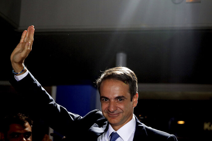 Greek opposition New Democracy conservative party leader Kyriakos Mitsotakis waves to his supporters after win in parliamentary elections at the New Democracy headquarters in Athens, on Sunday, July 7, 2019. Official results from nearly 60% of ballots counted showed the conservative New Democracy party of Kyriakos Mitsotakis winning comfortably with 39.7% compared to Tsipras' Syriza party with 31.5%. (AP Photo/Petros Giannakouris)