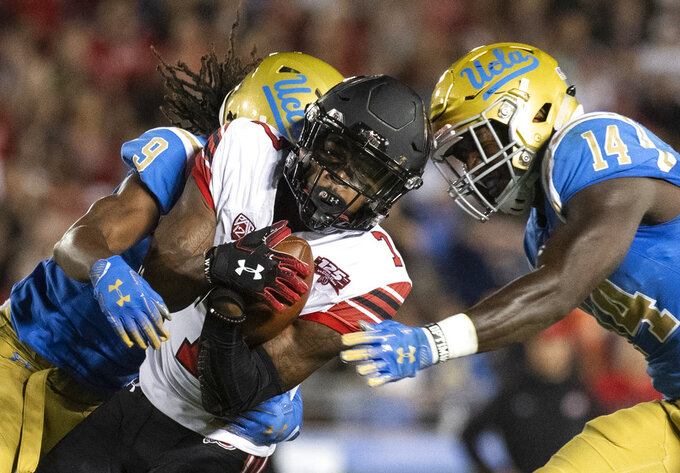 Utah wide receiver Demari Simpkins, center, tries to escape from UCLA defensive back Elijah Gates, left, and linebacker Krys Barnes during the first half of an NCAA college football game Friday, Oct. 26, 2018, in Pasadena, Calif. (AP Photo/Kyusung Gong)