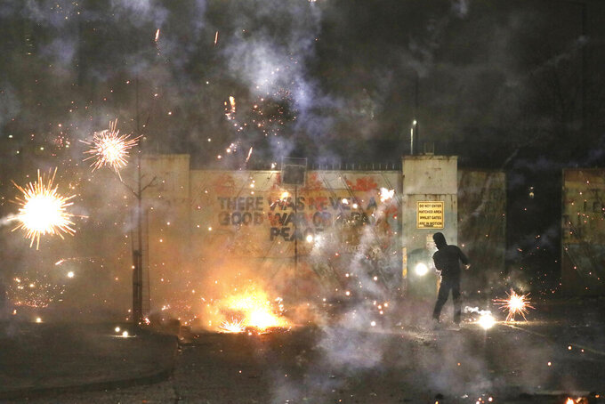A firework explodes as Nationalist and Loyalist rioters clash with one another at the peace wall on Lanark Way in West Belfast, Northern Ireland, Wednesday, April 7, 2021. The police had to close roads into the near by Protestant area as crowds from each divide attacked each other. (AP Photo/Peter Morrison)