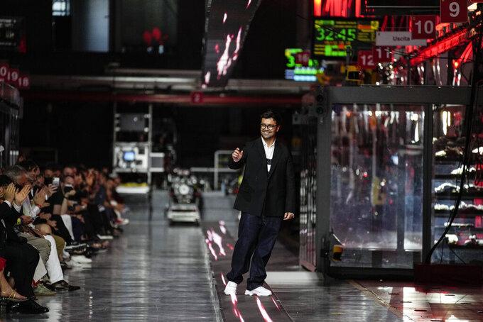 Designer Rocco Iannone accepts applause at the conclusion of the Ferrari women's and men's Spring Summer 2022 collection, in Maranello, Italy, Sunday, June 13, 2021. (AP Photo/Antonio Calanni)