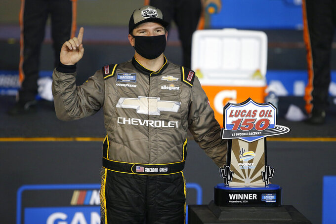 Sheldon Creed poses with the race trophy in victory lane after winning the NASCAR Truck Series auto race at Phoenix Raceway, Friday, Nov. 6, 2020, in Avondale, Ariz. With the victory Creed also captured the season championship. (AP Photo/Ralph Freso)
