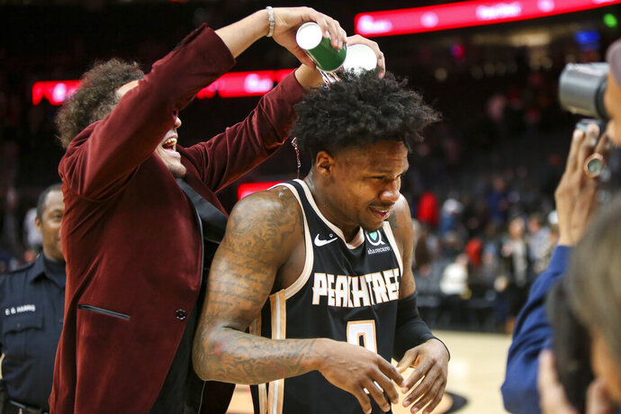 Atlanta Hawks guard Trae Young, left, pours water on guard Brandon Goodwin (0) after a 102-95 victory in an NBA basketball game against the Los Angeles Clippers, Wednesday, Jan. 22, 2020, in Atlanta. (AP Photo/Brett Davis)