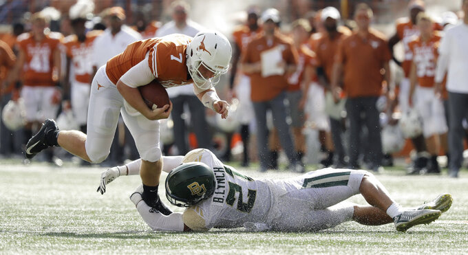 Texas quarterback Shane Buechele (7) is tripped by Baylor safety Blake Lynch (21) during the first half of an NCAA college football game, Saturday, Oct. 13, 2018, in Austin, Texas. (AP Photo/Eric Gay)