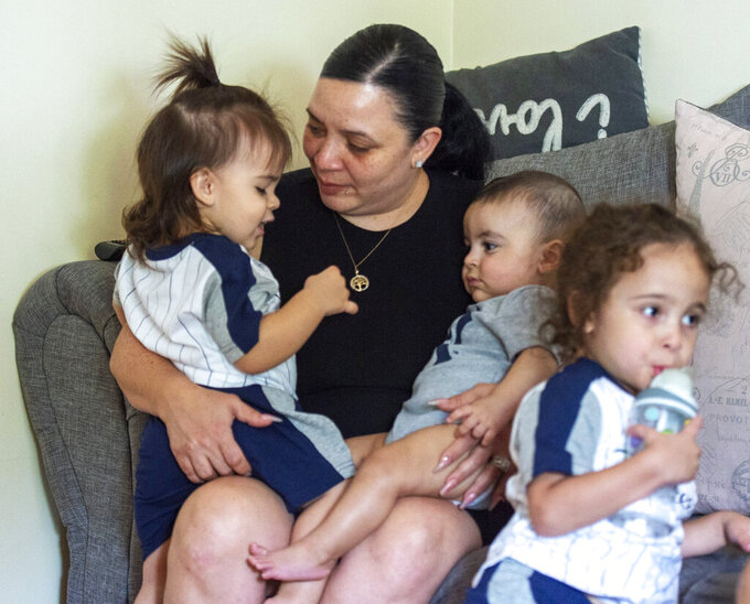 Zeneida Torres holds J.T., 18 months, left,  Justin, 8, months and Jacob, 4,  in the family living room, Tuesday, Aug. 31, 2021 in Bethlehem, Pa.. Zeneida Torres, of Bethlehem lost her sister Jackie to COVID-19 in December. Torres adopted Jackie's sons, ages 4, 18 months and 8 months, all of whom have special needs. (April Gamiz/The Morning Call via AP)