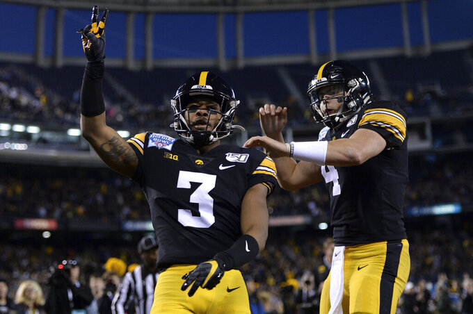 Iowa wide receiver Tyrone Tracy Jr., left, is congratulated by quarterback Nate Stanley after scoring a touchdown during the first half of the Holiday Bowl NCAA college football game against Southern California, Friday, Dec. 27, 2019, in San Diego. (AP Photo/Orlando Ramirez)