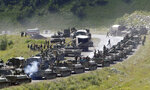 FILE - In this Saturday, Aug. 9, 2008 file photo, a column of Russian armored vehicles seen on their way to the South Ossetian capital Tskhinvali somewhere in the Georgian breakaway region, South Ossetia, Georgia. The European Court of Human Rights ruled Thursday, Jan. 21, 2021 that Russia was responsible for a swathe of violations in Georgia's breakaway regions after the 2008 Russia-Georgia war. (AP Photo/Musa Sadulayev, File)