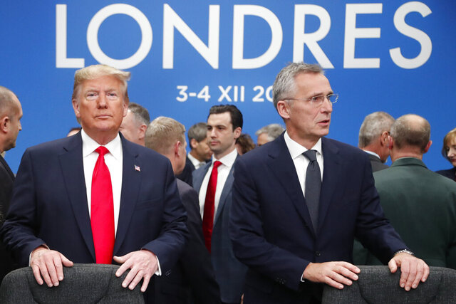 In this Dec. 4, 2019, photo, U.S. President Donald Trump and NATO Secretary General Jens Stoltenberg wait to take their seats prior to a NATO leaders meeting at The Grove hotel and resort in Watford, Hertfordshire, England. Three years into the Trump presidency, America's new place in the world is coming into focus, with influence waning from NATO meeting rooms to the Middle East to the capital cities of key allies. And in many ways, that's just fine with the White House. (AP Photo/Frank Augstein)