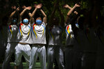Workers wearing face masks to protect against COVID-19 do group exercises at a park in Beijing, Tuesday, May 25, 2021. (AP Photo/Mark Schiefelbein)