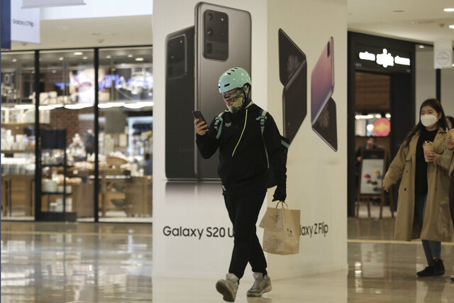 In this Tuesday, April 28, 2020 photo, a man passes by an advertisement of Samsung Electronics' Galaxy S20 Ultra and Galaxy Z Flip smartphone at its shop in Seoul, South Korea. Samsung Electronics Co. said Wednesday, April 29, its operating profit for the first three months of 2020 rose 3.4% from a year earlier driven by increasing demands for computer chips. However, the company predicted its profit would decline in the current quarter with the coronavirus pandemic eating into global sales of smartphones, TVs and other products. (AP Photo/Ahn Young-joon)