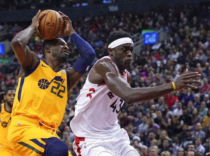 Utah Jazz's Patrick McCaw (22) collides with Toronto Raptors' Pascal Siakam (43) during first half NBA basketball action in Toronto, Sunday, Dec. 1, 2019. (Hans Deryk/The Canadian Press via AP)