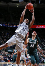 Penn State's Lamar Stevens, left, pulls down a rebound against Michigan State's Malik Hall (25) during the second half of an NCAA college basketball game Tuesday, Feb. 4, 2020, in East Lansing, Mich. Penn State won 75-70. (AP Photo/Al Goldis)