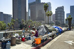 FILE - In this May 10, 2018 file photo, a homeless person sits at his tent along the Interstate 110 freeway downtown Los Angeles. Mayor Eric Garcetti is paying a political price for the city's homeless crisis. An effort is underway to recall the two-term Democrat from office prompted by widespread complaints about homeless encampments throughout the city. Figures released earlier this month showed a 16% jump in LA's homeless population over the last year, pegging it at 36,300, the size of a small city. (AP Photo/Richard Vogel, File)