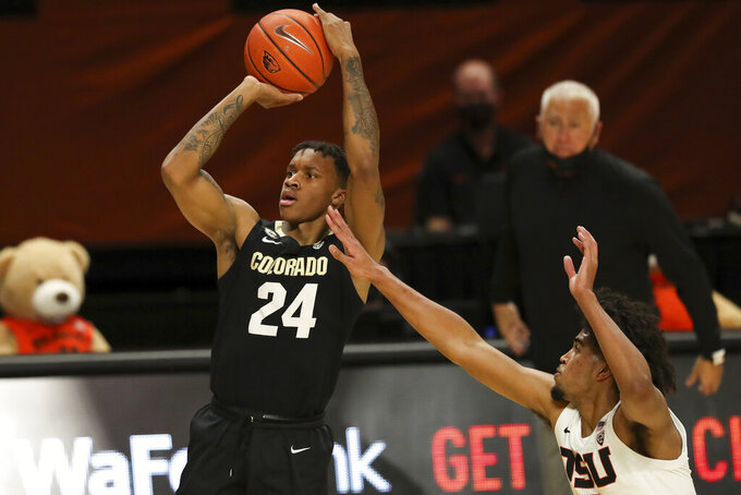 Oregon State's Ethan Thompson, right, tries to block a shot by Colorado's Eli Parquet (24) during the first half of an NCAA college basketball game in Corvallis, Ore., Saturday, Feb. 20, 2021. (AP Photo/Amanda Loman)