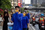 Office workers and construction workers with face masks walk in a side walk in Bangkok, Thailand, Thursday, Sept. 3, 2020. Thailand's prime minister on Wednesday congratulated his countrymen on the nation having achieved 100 days without a new confirmed locally transmitted case of the coronavirus, even as security along the border with Myanmar is being stepped up as a measure against the disease. (AP Photo/ Gemunu Amarasinghe)