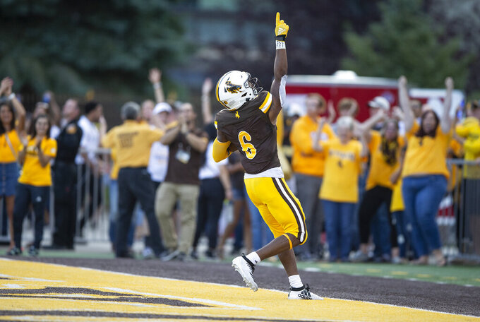 Wyoming running back Xazavian Valladay celebrates a touchdown run against Missouri during the second quarter of an NCAA college football game Saturday, Aug. 31, 2019, in Laramie, Wy. (AP Photo/Michael Smith)