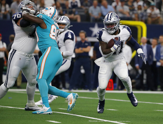 Dallas Cowboys' Zack Martin,left, helps against pressure from Miami Dolphins' Charles Harris, center, as running back Ezekiel Elliott (21) runs the ball in the first half of a NFL football game in Arlington, Texas, Sunday, Sept. 22, 2019. (AP Photo/Michael Ainsworth)