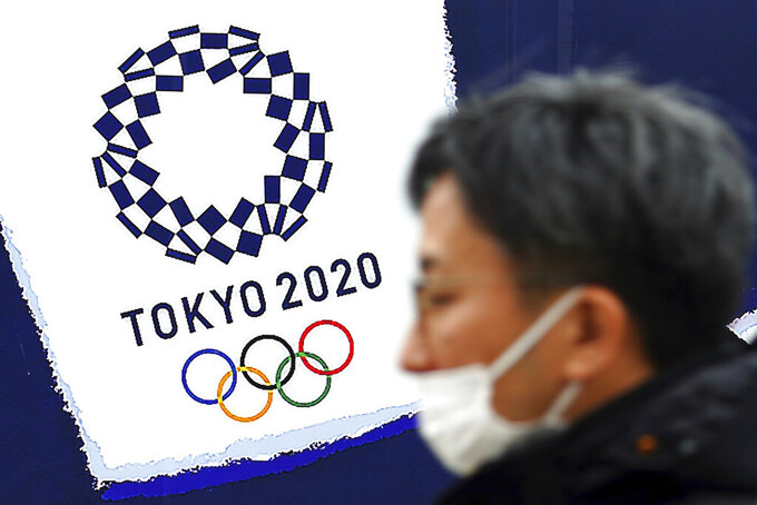 A man wearing a protective mask to help curb the spread of the coronavirus stands guard near a logo of Tokyo 2020 Olympic games in Tokyo on Feb. 1, 2021. Organizers and the International Olympic Committee pushed ahead Wednesday, April 28, 2021 with plans to open the postponed Tokyo Olympics in just under three months, unveiling the latest set of rule books to show how the games can be held during a pandemic. (AP Photo/Eugene Hoshiko)