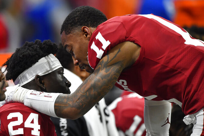 Oklahoma wide receiver Jadon Haselwood (11) speaks with Oklahoma running back Marcus Major (24) during the second half of the Peach Bowl NCAA semifinal college football playoff game against LSU, Saturday, Dec. 28, 2019, in Atlanta. LSU won 63-28. (AP Photo/John Amis)