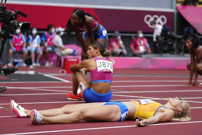Viktoriya Tkachuk, of Ukraine, lies on the track after the final of the women's 400-meter hurdles at the 2020 Summer Olympics, Wednesday, Aug. 4, 2021, in Tokyo. (AP Photo/Matthias Schrader)